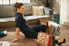 Kvinna med shoppingpåsar som sitter i lägenhet Fotografering för Bildbyråer
