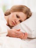 Kvinna med sjuka förkylningar för termometer, influensa, feber i säng Royaltyfri Fotografi
