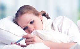 Kvinna med sjuka förkylningar för termometer, influensa, feber i säng Royaltyfri Foto