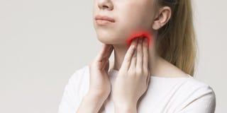 Kvinna med sköldkörtelproblemet som trycker på hennes hals royaltyfria foton