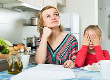 Kvinna med skrivbordsarbete och flickan i köket Arkivbild