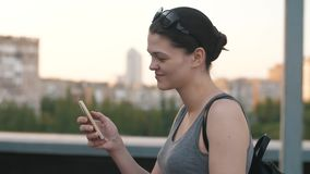 Kvinna med smartphon på taket arkivfilmer