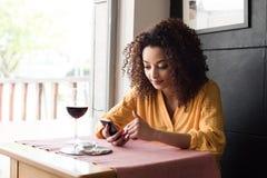 Kvinna med smartphonen i restaurang royaltyfri foto