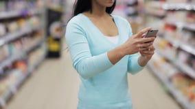 Kvinna med smartphonen på supermarket eller lagret arkivfilmer