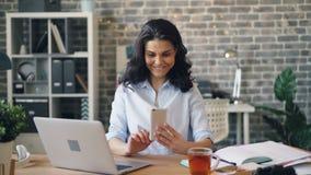 Kvinna med smartphonen som tycker om socialt massmedia på att le för tryckande på skärm för arbete arkivfilmer