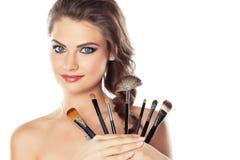 Kvinna med sminkborstar Arkivfoto