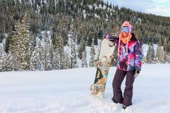 Kvinna med snowboarden i snön royaltyfri foto