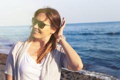 Kvinna med solglasögon som ler på baachen som wallpaperen för hav för bakgrund den blåa praktiska för Arkivbilder