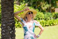 Kvinna med sommarhatten och solglasögon som står under palmträdet Arkivfoton