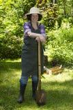 Kvinna med spaden i en trädgård Arkivbild