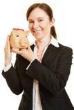 Kvinna med spargrisen som pengarinvestering Fotografering för Bildbyråer