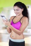 Kvinna med sportswearen genom att använda smartphonen Arkivbild