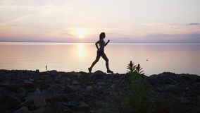 Kvinna med spring på stranden i ultrarapid på solnedgången lager videofilmer
