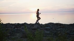 Kvinna med spring på stranden i ultrarapid på solnedgången stock video