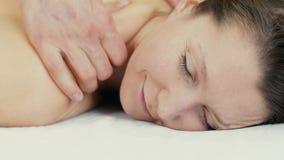 Kvinna med stängda ögon som får massage arkivfilmer