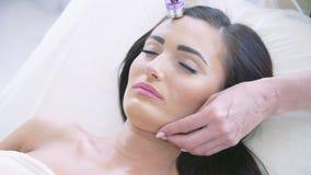 Kvinna med stängda ögon som får rf-lyfta i en skönhetsalong arkivfilmer