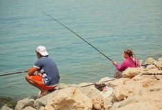 Kvinna med stång- och manfiske på en fjärd med blått vatten av det Aegean havet Royaltyfri Foto