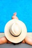 Kvinna med strandhatten som kopplar av vid pölen på den exotiska semesterorten Royaltyfri Foto