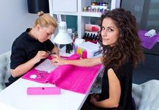 Kvinna med stylisten på manikyr royaltyfri foto