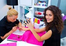 Kvinna med stylisten på manikyr royaltyfria foton