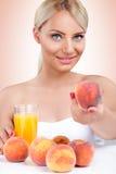 Kvinna med sund persikafruktsaft Arkivbilder