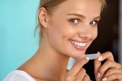 Kvinna med sunda vita tänder genom att använda tänder som gör vit remsan Royaltyfri Bild