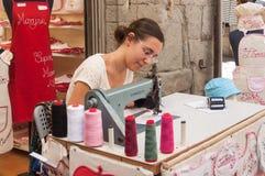 Kvinna med symaskinen som broderar förnamnet på tyg för turister i gatan Arkivbild