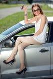 Kvinna med tangenter och licens nära hennes bil royaltyfri foto