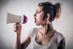 Kvinna med tatueringar genom att använda en megafon Arkivbilder