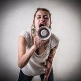 Kvinna med tatueringar genom att använda en megafon Royaltyfria Bilder