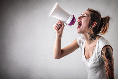 Kvinna med tatueringar genom att använda en megafon Royaltyfria Foton