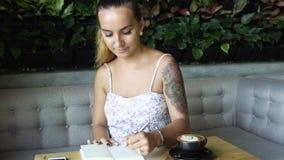 Kvinna med tatueringen som studerar och skriver i anteckningsbok Kvinnligt sammanträde på tabellen i mysigt kafé stock video
