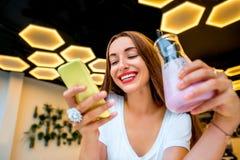 Kvinna med telefonen och drinken i modern inre Arkivbilder
