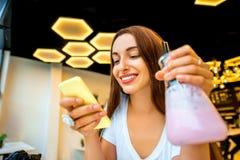 Kvinna med telefonen och drinken i modern inre Arkivfoto
