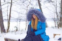Kvinna med termoset i vinterskog Arkivbild