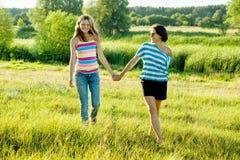 Kvinna med tonårigt gå för dotter i naturinnehavhänder Arkivfoton