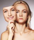 Kvinna med två framsidor. Maskering Arkivfoto