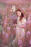 Kvinna med ugglan på fältet av rosa blommor royaltyfri foto