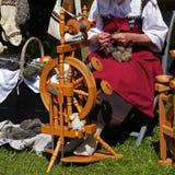 Kvinna med ull på det traditionella snurrhjulet på ett medeltida Arkivbilder