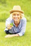Kvinna med växt av släktet Trifolium Arkivfoto