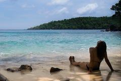Kvinna med vått långt hår som tycker om och solbadar på en ursprunglig blått-gräsplan strand i South East Asia royaltyfri bild