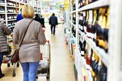 Kvinna med vagnen i supermarket Arkivfoton