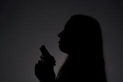 Kvinna med vapnet i mörker Arkivfoton