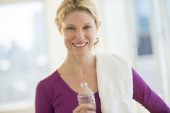 Kvinna med vattenflaskan och handduken som ler i klubba royaltyfri fotografi
