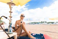 Kvinna med vattenpipan på stranden Arkivbilder