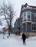 Kvinna med vinterkläder som går ner entäckt gata i en snöstorm royaltyfri bild