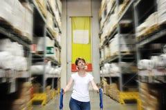 Kvinna mellan hyllor av hemförbättringlagret Royaltyfri Fotografi