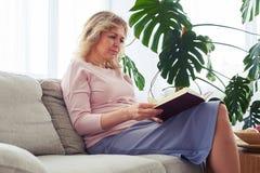 Kvinna myndig 30-40 som koncentrerar på läseboken Arkivfoto