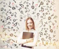 Kvinna nära den vita väggen med utbildningssymboler som tonas Royaltyfri Fotografi