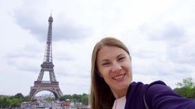 Kvinna nära Eiffeltorn genom att använda mobilen som talar via budbäraren app Le turist- kvinnaresande i Europa arkivfilmer